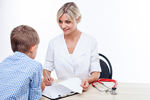 Attractive doctor is talking with a boy. They are sitting at the table and smiling. The woman is looking at the child happily and writing down some notes. Isolated on background